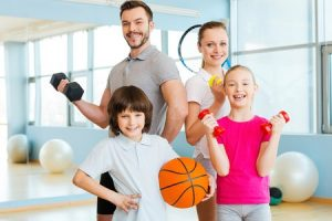 37824006 - happy and sporty. happy family holding different sports equipment while standing close to each other in health club