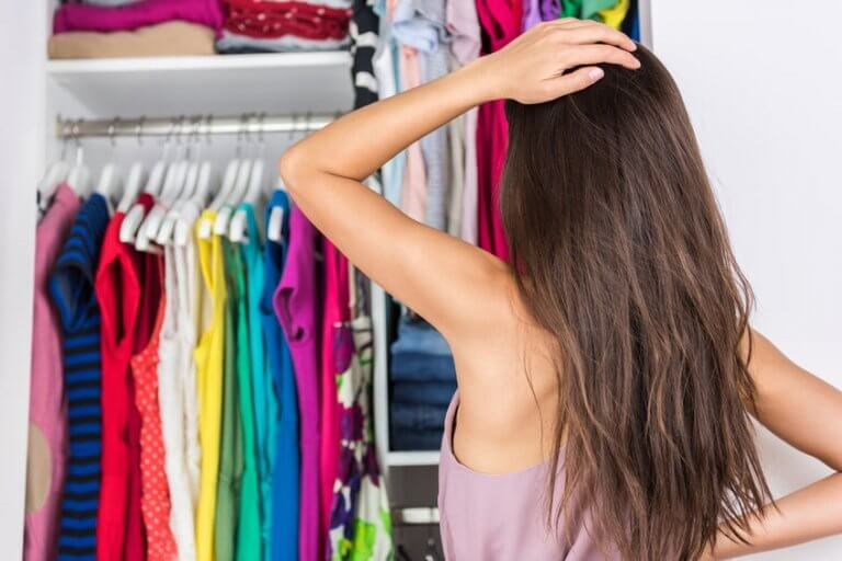 55645911 - home closet indecision woman choosing her fashion outfit on clothing rack. shopping spring cleaning concept. morning woman having too many clothes thinking of what to wear in organized clean walk-in.